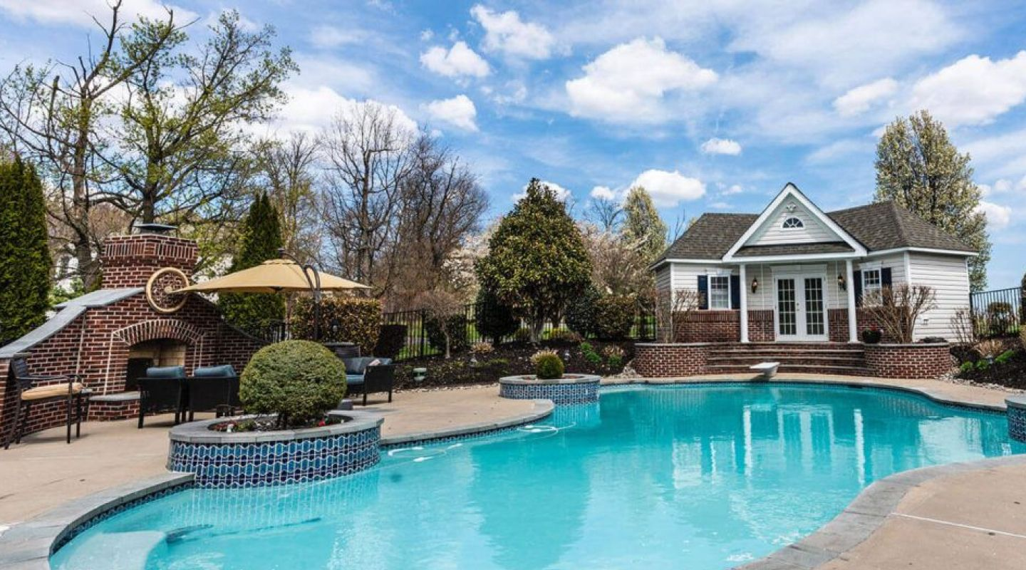 Image of a backyard swimming pool with a pool house and outdoor fireplace in the background