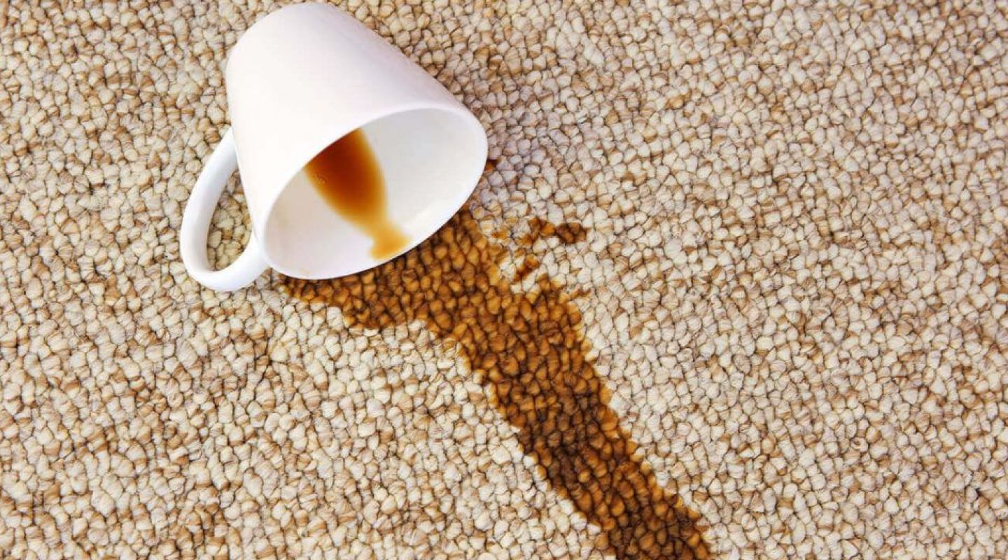 Image of a cup of coffee that spilled on a carpet causing the carpet to stain