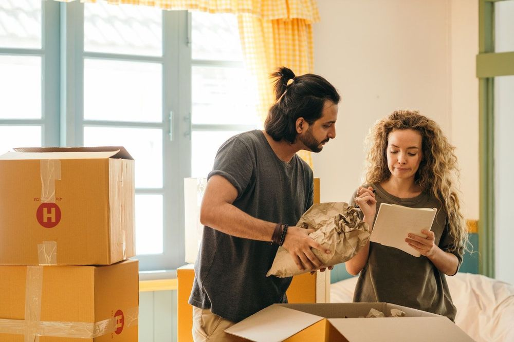 Image of a man packing a moving box with a woman standing next to him holding a notepad and pen