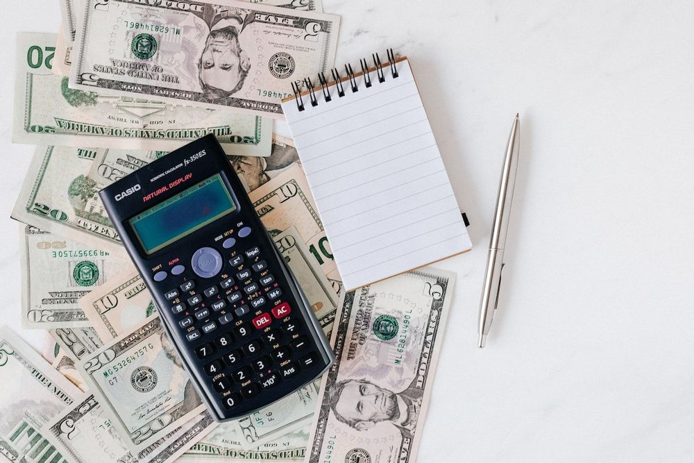 Image of a calculator, notepad, and pen sitting on a pile of five, ten, and twenty dollar bills