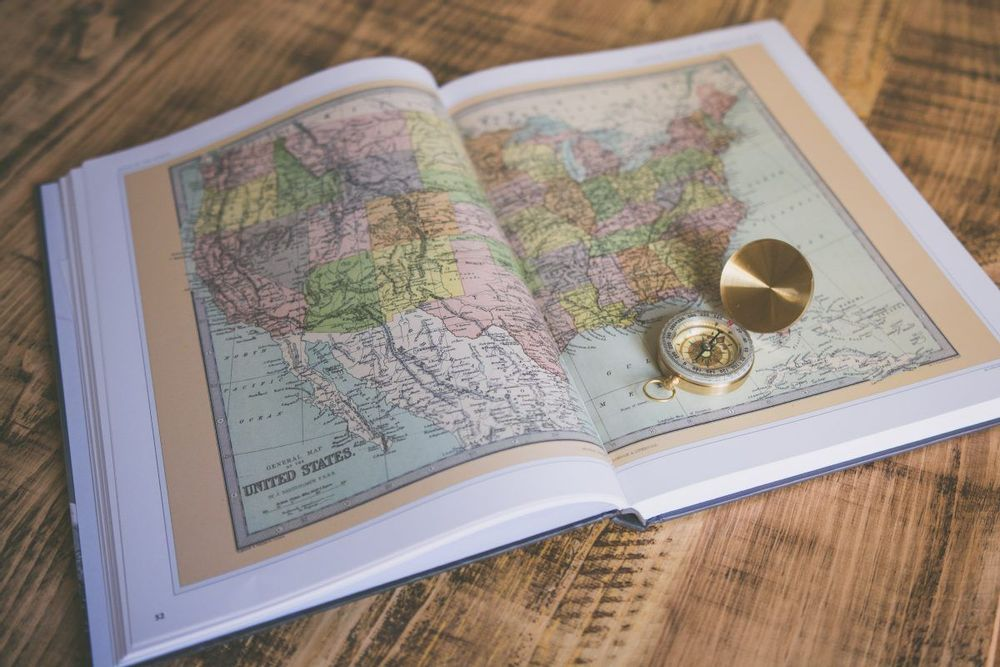 Image of an open book with a map of the united states on the page and a compass sitting on top of the book