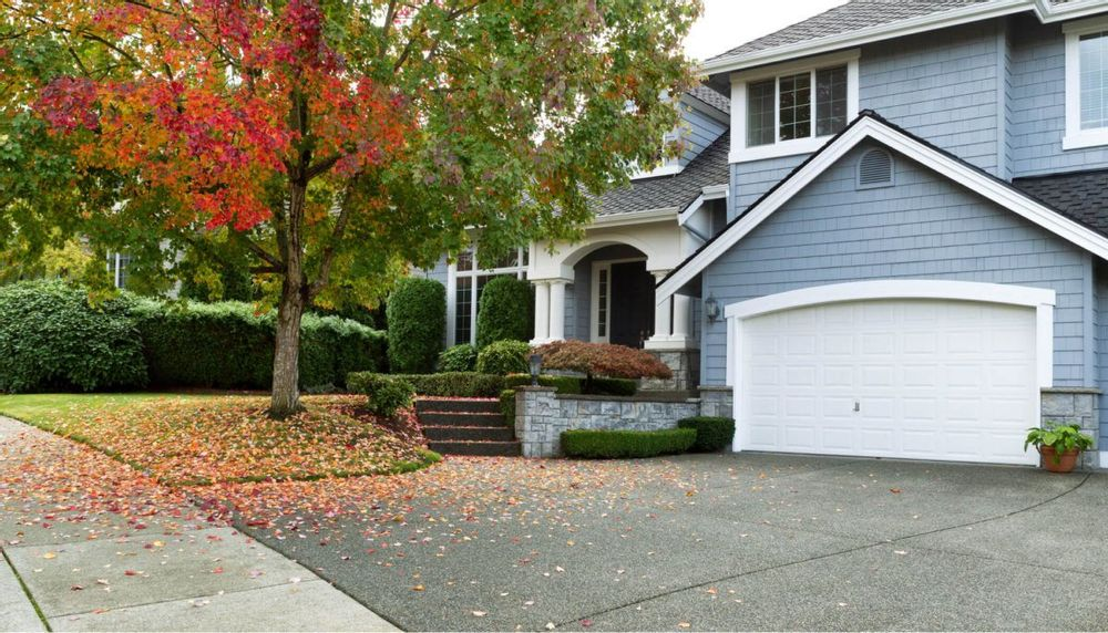 An image of the front of a single family home and a tree that is in the front yard whose leaves are changing colors