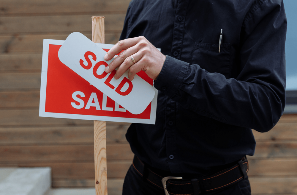 """Image of a person putting a """"sold"""" sticker over a """"for sale"""" sign"""