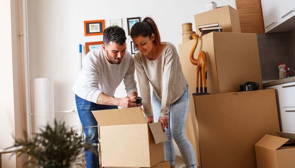 Image of a man and a woman packing a moving box with other moving boxes in the background