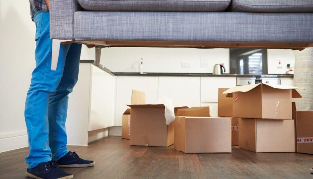Image of a man lifting a couch with moving boxes in the background