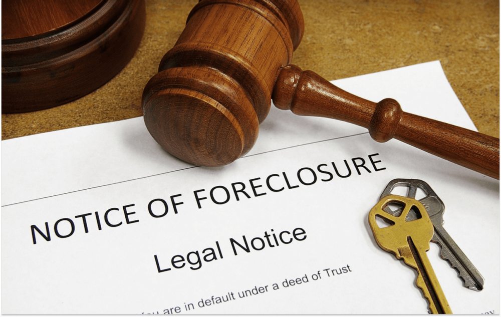 """Image of a gavel and a set of house keys resting on top of a piece of paper that has the words """"Notice of Foreclosure"""""""