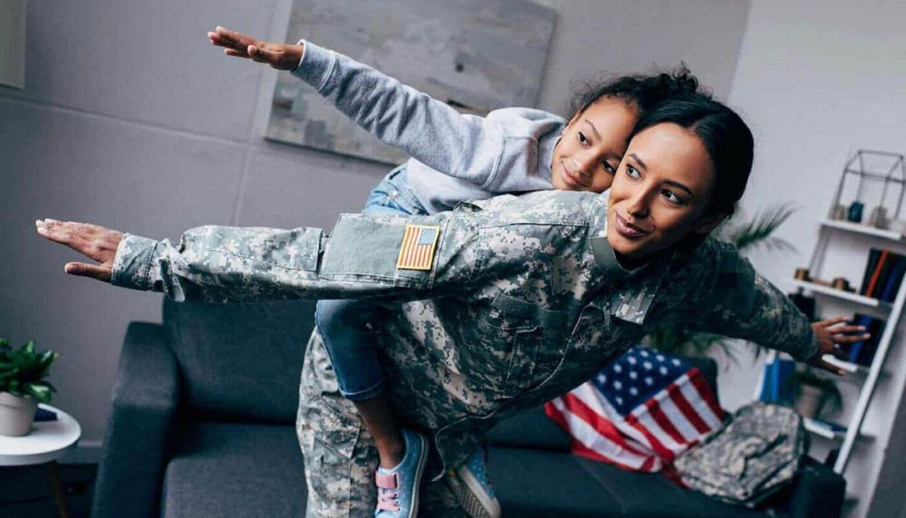 Image of a mother dressed in a military uniform with her daughter on her back