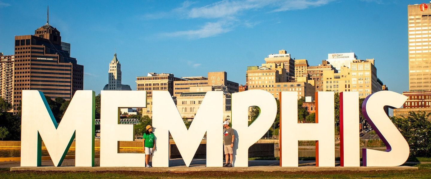 "Image of a man and a woman standing in front of a sign that says the words ""Memphis"""