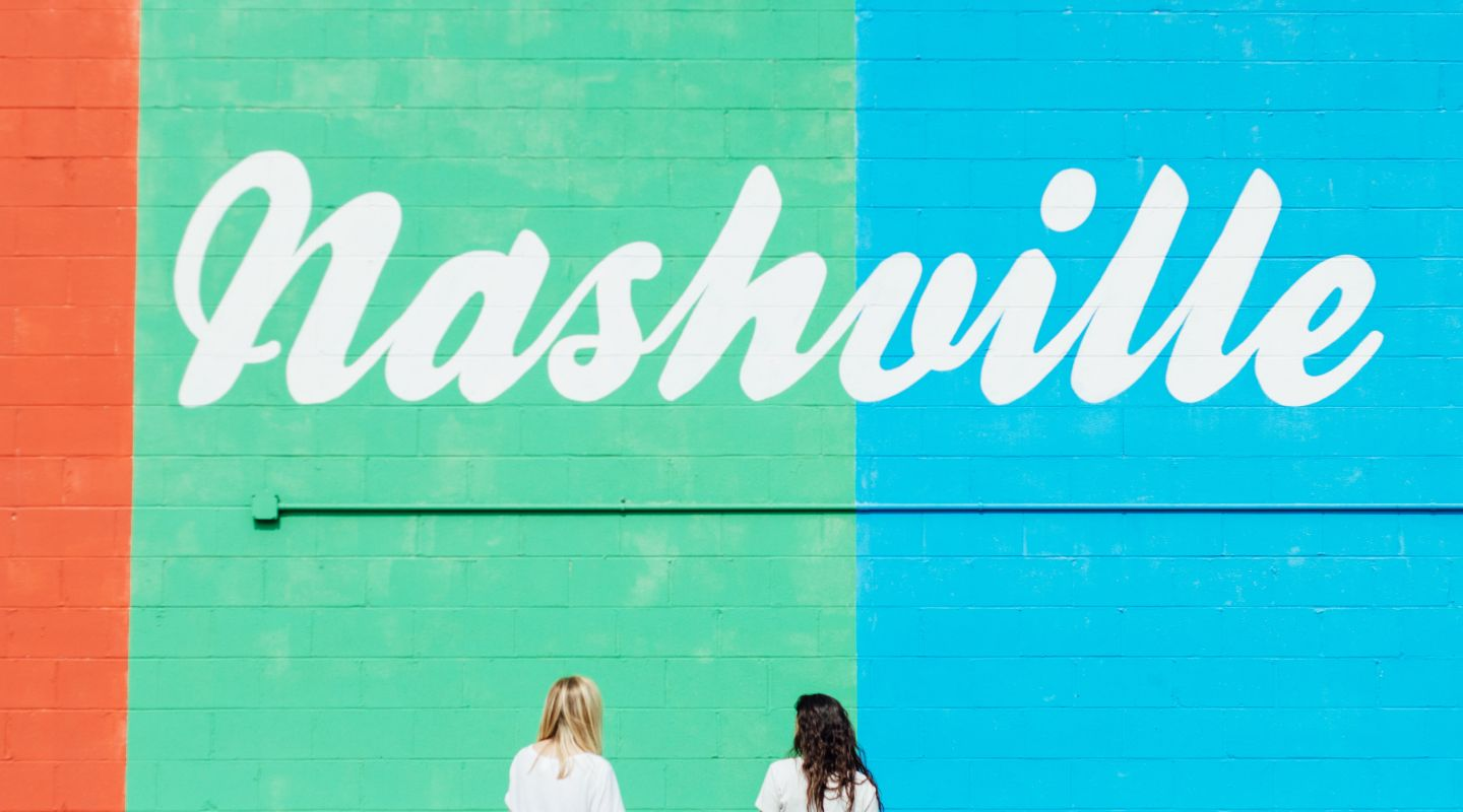 Image of two women standing in front of a mural that says Nashville
