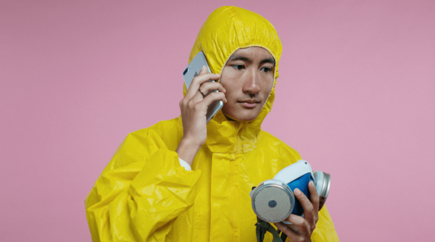 An image of a man holding a cell phone in one hand while also holding a respiratory mask in the other hand