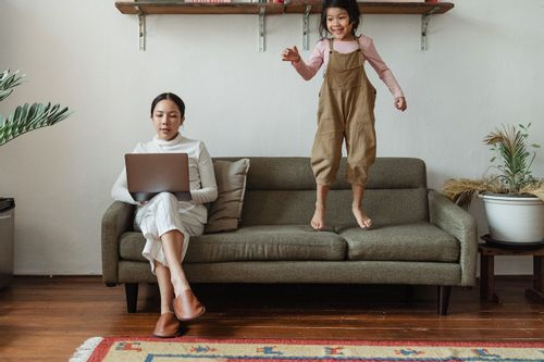Image of a woman sitting on a couch looking at her laptop while her daughter jumps on the couch beside her