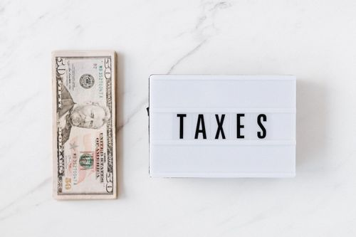 """Image of a fifty dollar bill sitting on a countertop with a sign that says """"taxes"""" on it"""