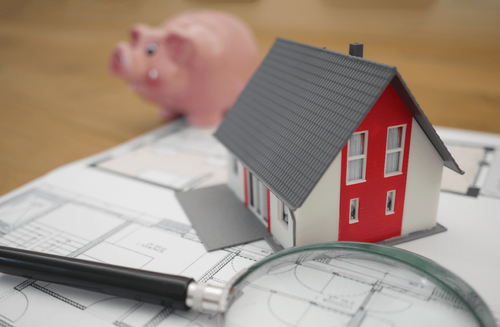 Image of a toy house, magnifying glass, and piggy bank sitting on top of a table.