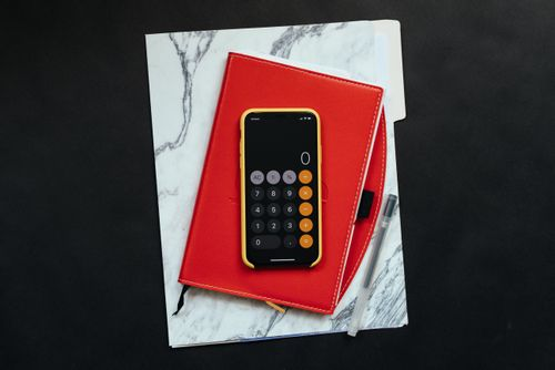 """Image of an iPhone with the """"calculator app"""" opened sitting on top of a notepad"""