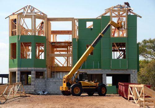 Image of a house under construction with construction equipment