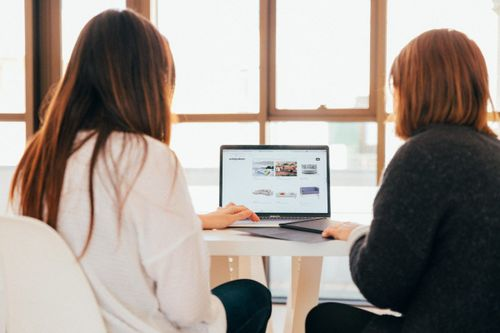 Image of two women looking at a laptop screen
