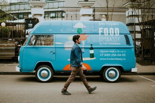 Image of a man walking in front of a food truck