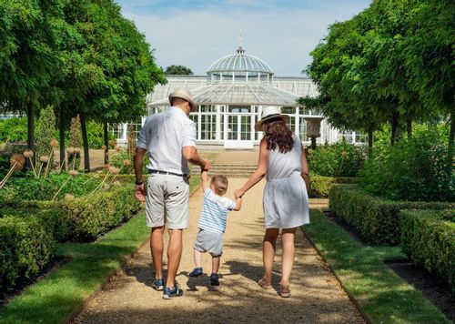 Image of a husband and wife holding hands with their son walking around a park