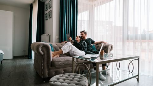 Image of a young couple sitting on a couch looking at an iPad