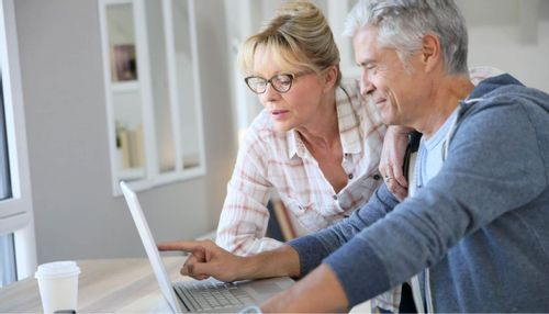 An image of an older couple looking at the screen of a laptop