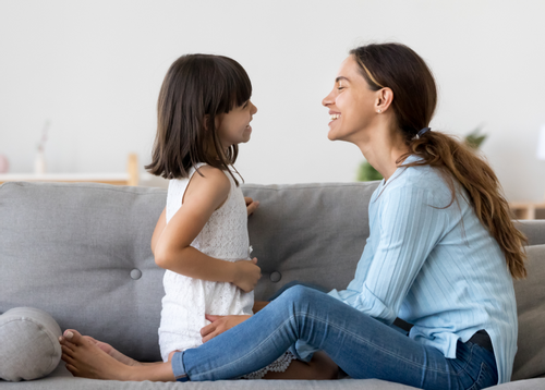 Image depicting a mother laughing on a couch with her daughter