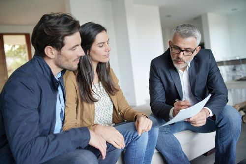 An image of a younger couple looking at a piece of paper that an older real estate agent is holding