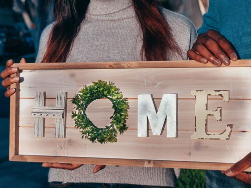 Image of a couple holding a sign that says 'home'.