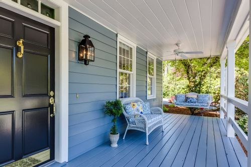 Image of a front porch with an outdoor couch and swing