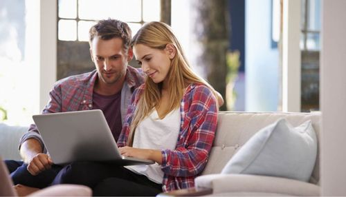 Image of a young couple sitting on a couch looking at a laptop